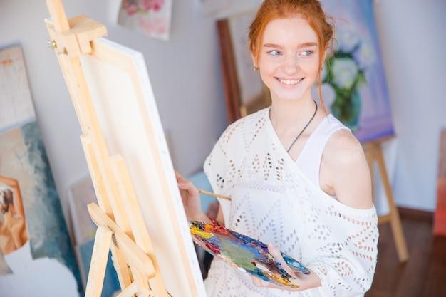 Felice adorabile giovane donna pittore che tiene tavolozza con colori ad olio e pittura su tela in studio d'arte