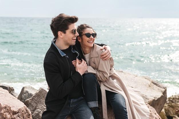 Felice bella coppia giovane che indossa cappotti seduti in spiaggia, tenendosi per mano, abbracciando
