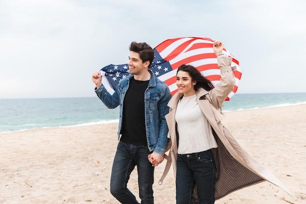 Felice bella coppia giovane che indossa cappotti camminando in spiaggia, tenendosi per mano, portando bandiera americana
