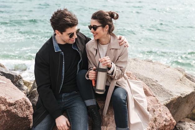 Felice bella coppia giovane che indossa cappotti camminando in spiaggia, tenendosi per mano, bevendo caffè dal thermos