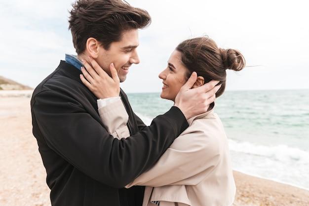 Felice bella coppia giovane che indossa cappotti camminando sulla spiaggia, tenendosi per mano, abbracciando