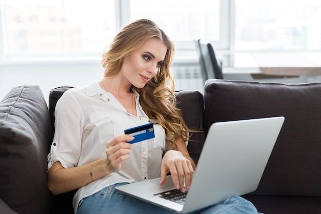 Felice bella giovane donna che fa acquisti su internet utilizzando la carta di credito a casa
