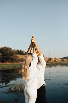 Amanti felici in spiaggia vicino al lago. la giovane coppia sta alzando le mani e sta baciando.