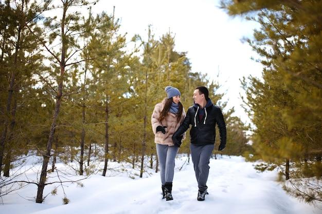 Gli amanti felici che tengono le mani camminano nella foresta di abeti nella neve