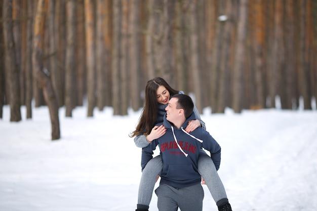 Amanti felici in inverno sullo sfondo del bosco innevato all'aperto