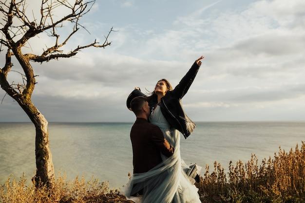 Felice coppia di innamorati divertendosi sul mare, ragazzo ha sollevato la ragazza tra le braccia e gira.