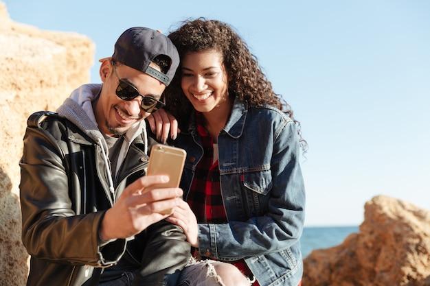 Coppie amorose felici che camminano all'aperto alla spiaggia che chiacchiera dal telefono.