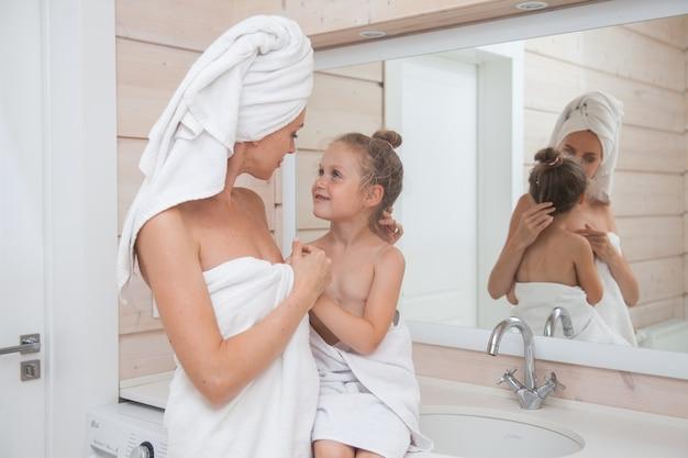 Felice famiglia amorevole madre e figlia con asciugamani trascorrere del tempo insieme in bagno bianco.