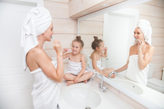 Madre di famiglia amorevole felice e piccola figlia con asciugamani lavarsi i denti in bagno bianco.