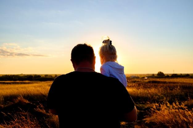 Felice famiglia amorevole. vista posteriore del papà che tiene la sua piccola figlia tra le braccia al tramonto all'aperto.