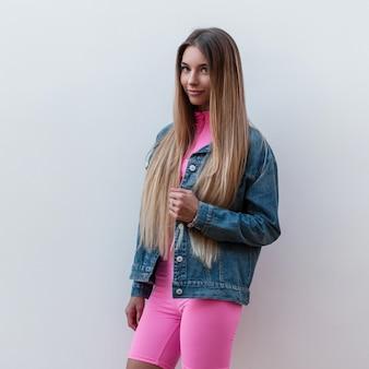 Felice lussuosa giovane donna in una giacca di jeans alla moda in eleganti pantaloncini rosa con un bel sorriso pone all'aperto vicino a un muro vintage. gioiosa ragazza urbana all'aperto in una calda giornata estiva. stile retrò.