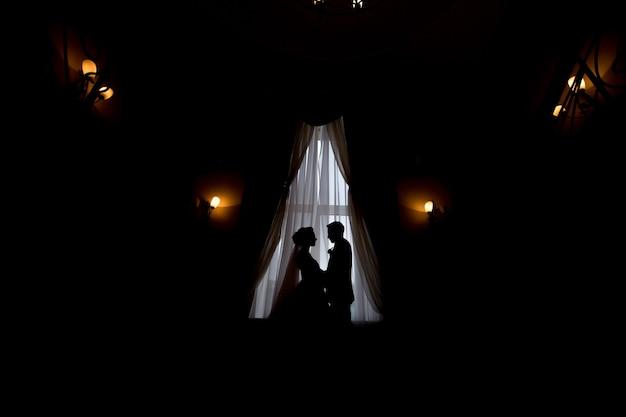 Felice sposa e sposo di lusso in piedi alla luce della finestra in una stanza ricca, momento tenero