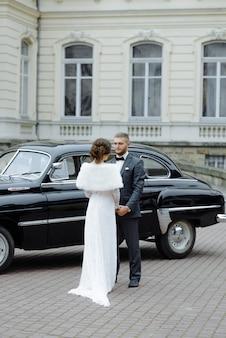 Coppie di lusso felici di nozze che baciano e che abbracciano vicino a retro con l'automobile del mazzo in autunno