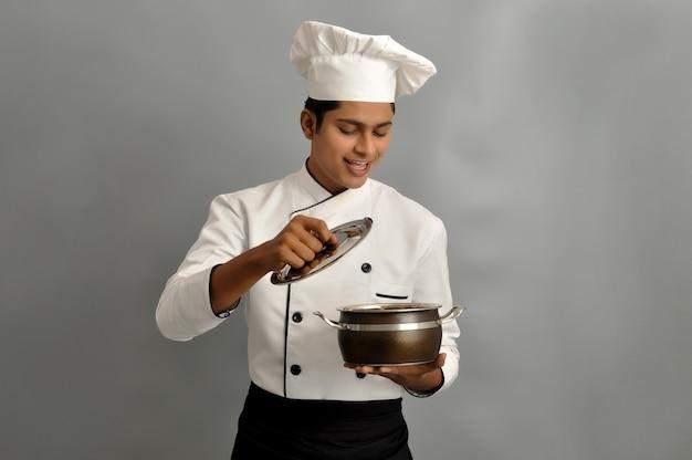 Felice chef maschio vestito in uniforme che tiene pentola guardando dentro