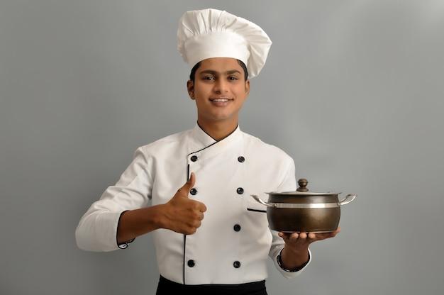 Felice chef maschio vestito in uniforme che tiene pentola con mostra pollice in alto