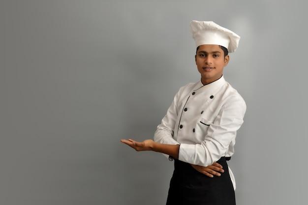 Felice chef maschio vestito in uniforme che tiene qualcosa sul palmo della mano