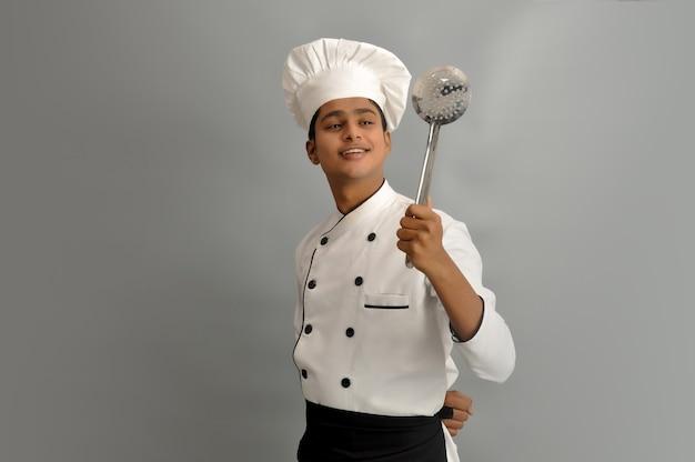 Felice chef maschio vestito in uniforme che tiene in mano skimmer in acciaio e guardando