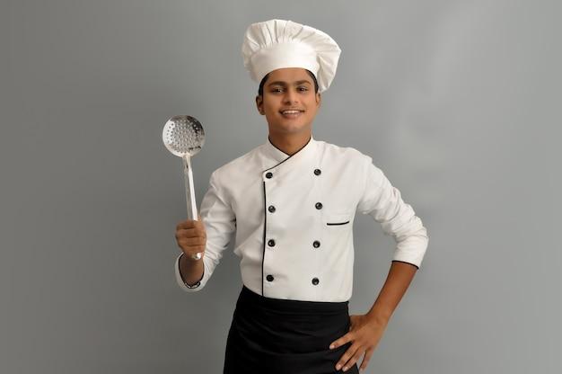 Felice chef maschio vestito in uniforme con skimmer in acciaio