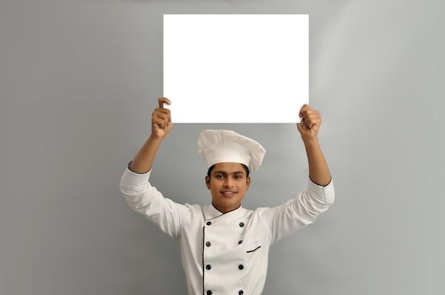 Felice chef maschio vestito in uniforme con banner pubblicitario bianco buon poster per annuncio