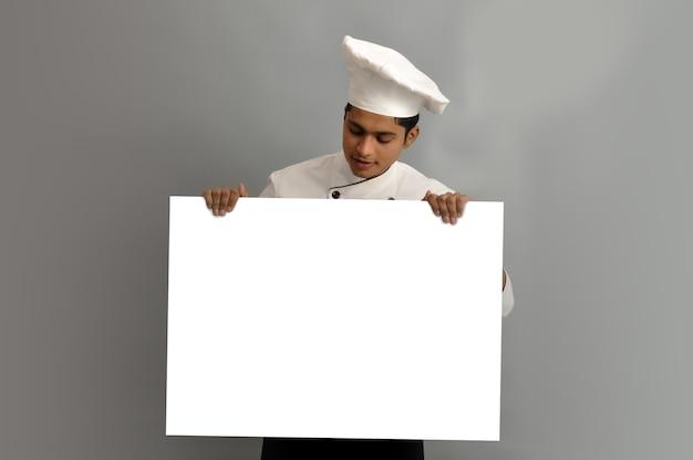 Felice chef maschio vestito in uniforme con striscione pubblicitario bianco che guarda a bordo