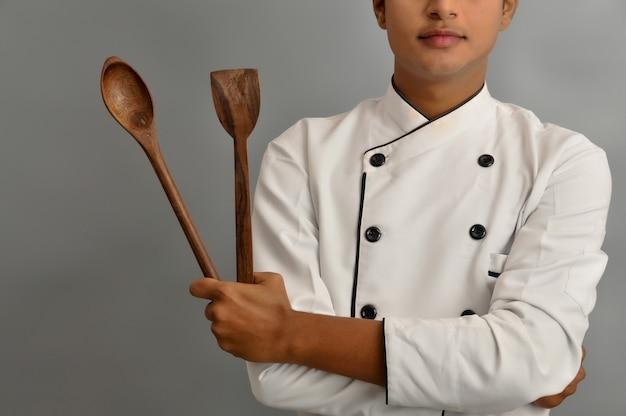 Felice chef maschio vestito in uniforme che tiene il cucchiaio di legno tra le braccia incrociate