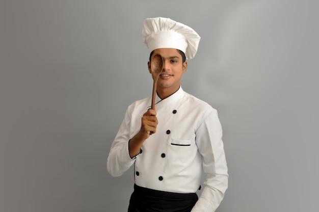 Felice chef maschio vestito in uniforme con cucchiaio di legno su un occhio