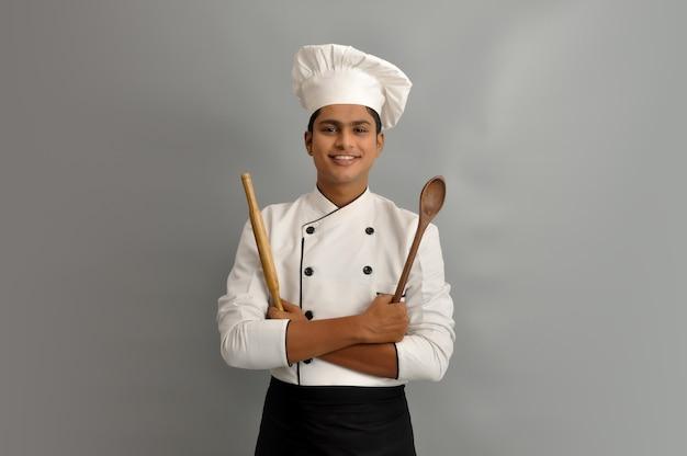 Felice chef maschio vestito in uniforme con cucchiaio di legno e rullo tra le braccia incrociate
