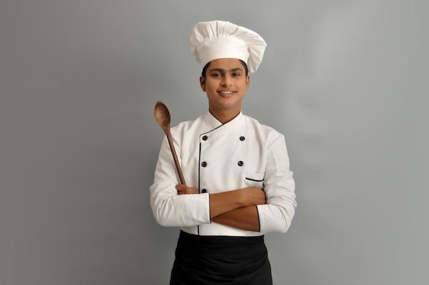 Cuoco unico maschio felice vestito in uniforme che tiene cucchiaio di legno