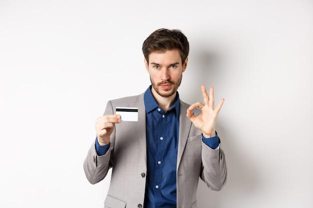 Cliente maschio felice in vestito di affari che mostra la carta di credito di plastica e segno giusto, sorridendo soddisfatto