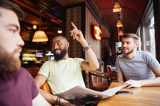 Amici maschi felici che chiamano il cameriere per fare l'ordine al ristorante