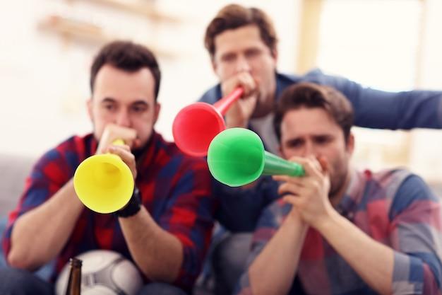 Amici maschi felici che tifano e guardano lo sport in tv