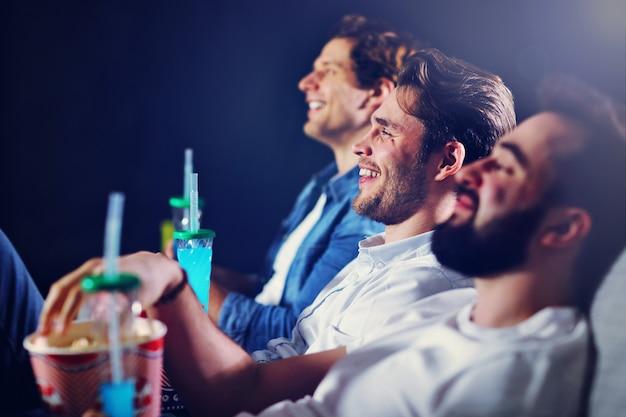 Amici maschi felici seduti al cinema guardano un film mangiando popcorn