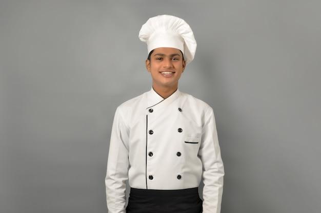 Cuoco unico indiano maschio felice che si leva in piedi sopra il muro grigio