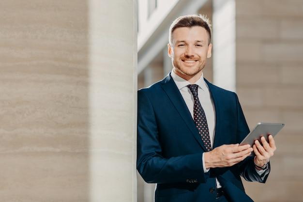 Manager maschio felice vestito in abito formale nero