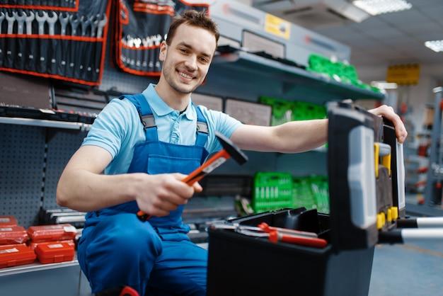 Felice lavoratore di sesso maschile in uniforme scegliendo la cassetta degli attrezzi nel negozio di utensili. scelta di attrezzature professionali in ferramenta, supermercato di strumenti