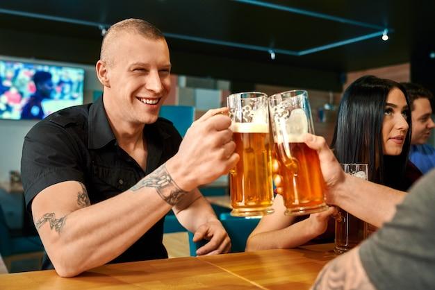 Uomo felice in camicia nera che si siede al tavolo e brindare con la birra con un amico seduto di fronte al pub. forte maschio tatuato che beve birra, ridendo e riposando nei fine settimana al bar. concetto di divertimento.