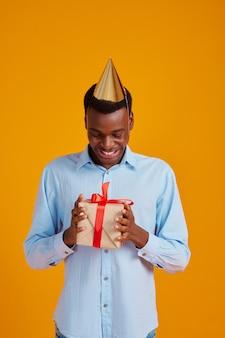Uomo felice in berretto con scatola regalo con nastri rossi. la persona di sesso maschile sorridente ha ricevuto una sorpresa, un evento o una festa di compleanno