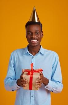 Uomo felice in berretto con scatola regalo con nastri rossi, sfondo giallo. la persona di sesso maschile sorridente ha ricevuto una sorpresa, un evento o una festa di compleanno