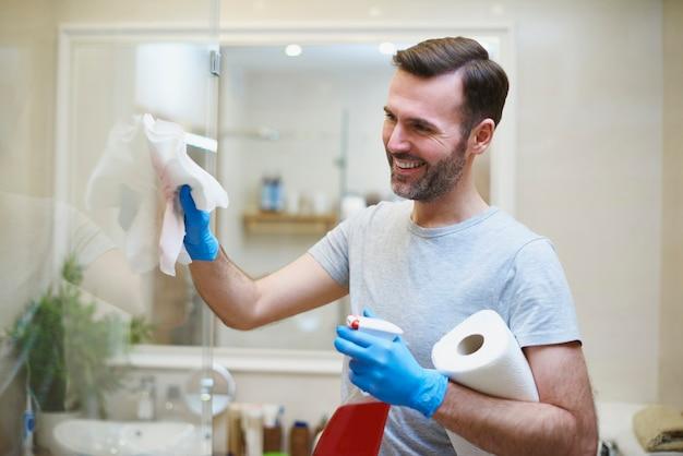 Uomo felice che pulisce la sua casa