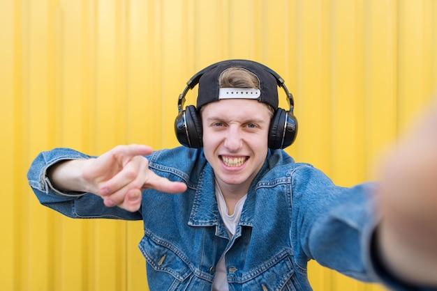 Uomo felice in una giacca di jeans e cuffie prende selfie su una parete gialla e mostra il segno di metalli pesanti