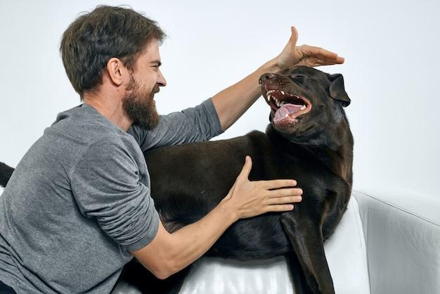 Uomo felice e cane sul divano in una stanza luminosa l'animale domestico è un amico dell'uomo