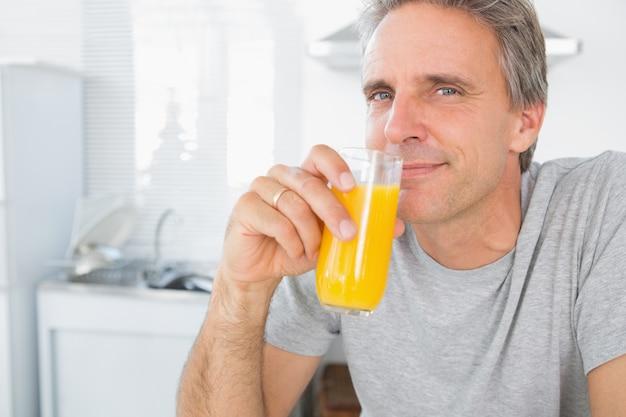 Uomo felice che beve il succo d'arancia in cucina