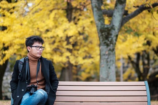 L'uomo felice si diverte al parco all'aperto nella stagione autunnale, viaggiatore asiatico in cappotto e macchina fotografica sullo sfondo di foglie di ginkgo giallo