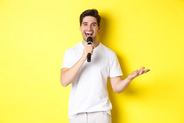 Intrattenitore uomo felice che si esibisce, parla al microfono, fa discorsi o spettacoli in piedi, in piedi su sfondo giallo.