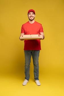 Uomo felice dal servizio di consegna in maglietta rossa e cappuccio che danno l'ordine del cibo e che tiene la scatola della pizza isolata sopra la parete gialla