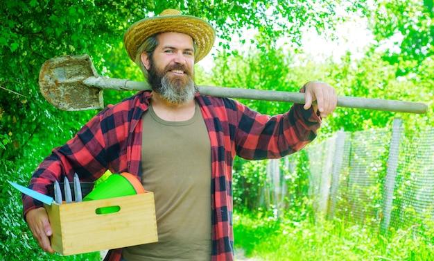 Uomo felice in giardino con attrezzi da giardinaggio. giardiniere professionista maschio.