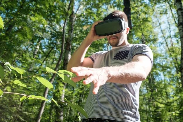 Uomo felice che ottiene esperienza utilizzando occhiali vr-headset della realtà virtuale nella foresta