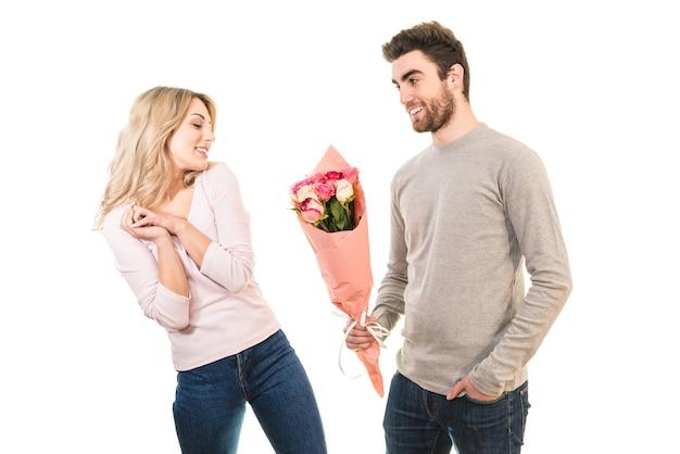 L'uomo felice che dà fiori per un'amica sullo sfondo bianco