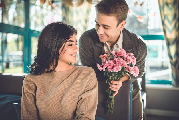 L'uomo felice che regala fiori a una donna al ristorante