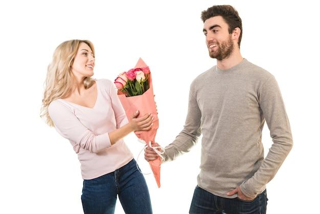L'uomo felice che dà fiori per una donna sullo sfondo bianco